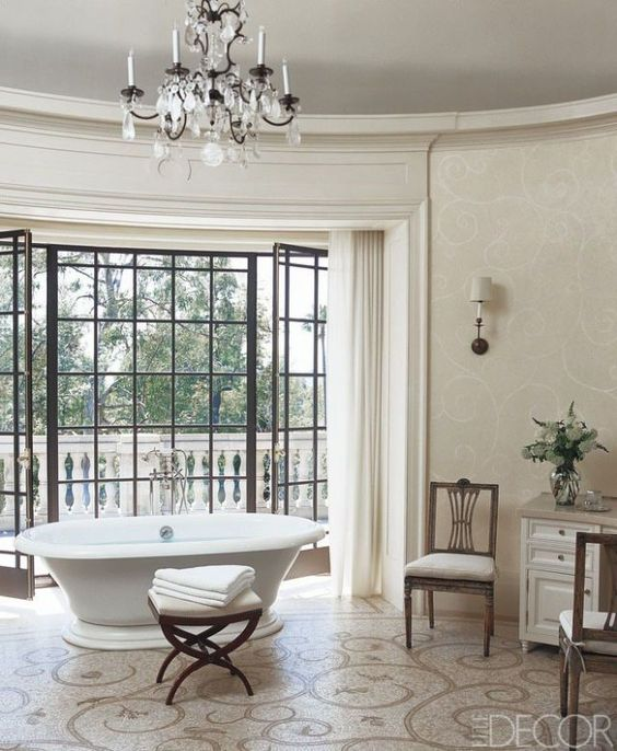 a neutral Parisian bathroom with a crystal chandelier, a chic vintage bathtub, a patterned floor and elegant furniture