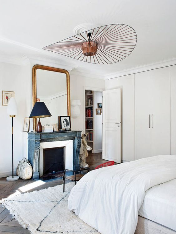 a neutral Parisian bedroom with a blue non workign fireplace, a statement lamp, a chic mirror and an antique wooden chair