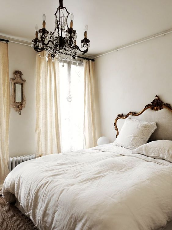 a neutral Parisian bedroom with a refined bed, a crystal chandelier, a mirror and flowy draperies