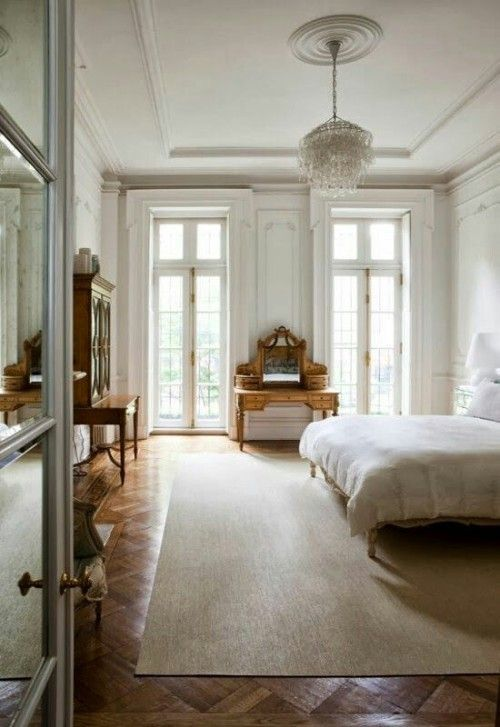 a neutral Parisian bedroom with antique wooden furniture, a crystal chandelier and large windows to fill the space with light
