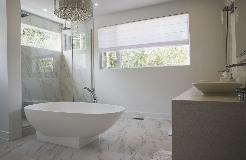 a neutral transitional bathroom with marble tiles on the floor and in the shower and a luxurious modern chandelier