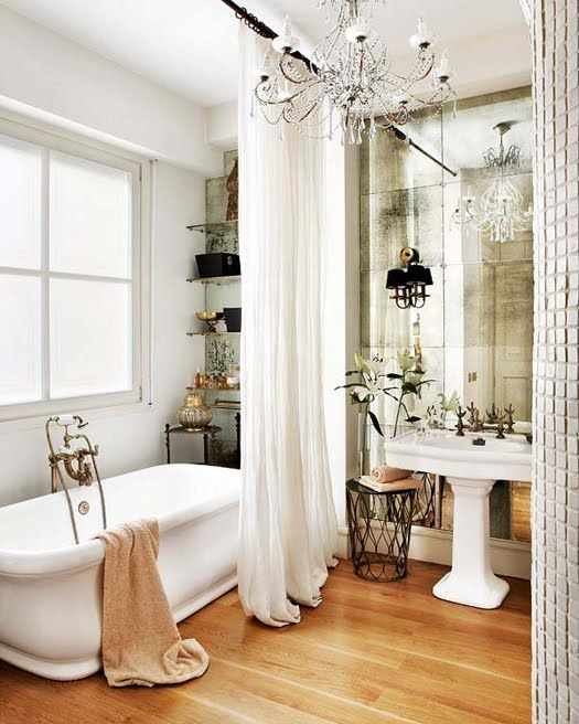 a refined Parisian bathroom with a mirror wall, a crystal chandelier, a tub, open shelves and a sink