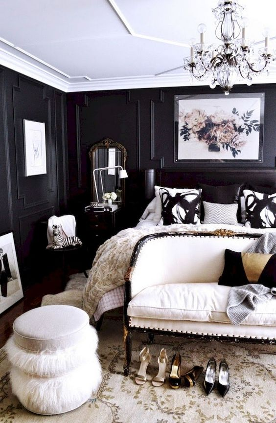 a refined and luxurious black and white bedroom with paneled walls, a black bed, a white upholstered loveseat and a fluffy ottoman