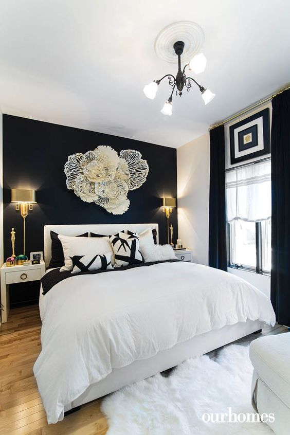 a refined black and white bedroom with a statement wlal, a flower inspired installation, a white bed and gorgeous wall lamps