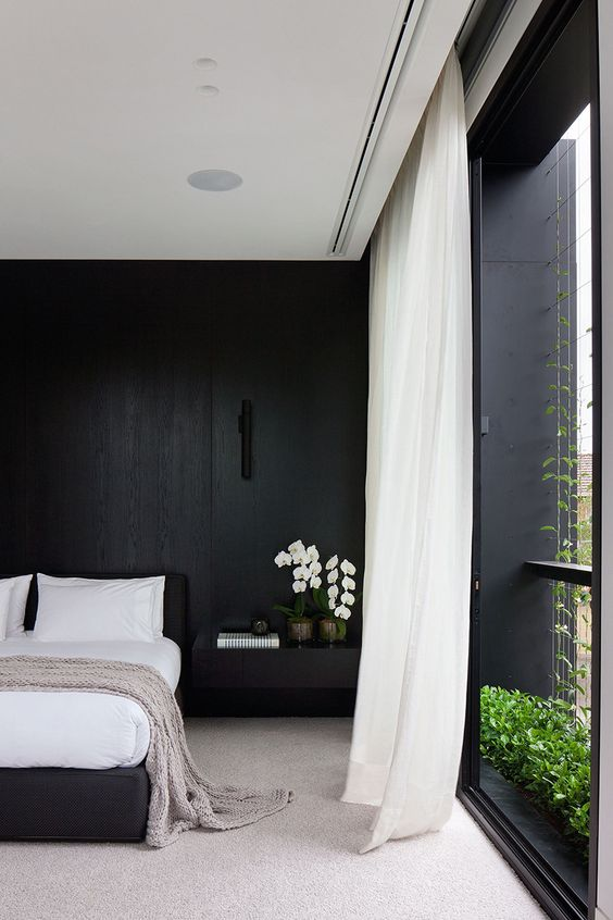 a refined minimalist black and white bedroom with a statement wall, a black bed, white curtains and stylish bedding