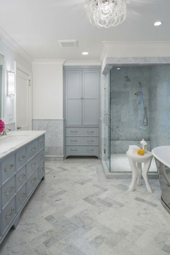 a relaxing bathroom done in greys and neutrals, with a chic chandelier, stylish vintage storage units and marble tiles
