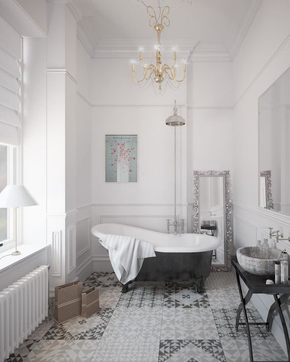 a stylish Parisian bathroom with a mosaic floor, elegant chandelier, a clawfoot tub, a side table and lamps