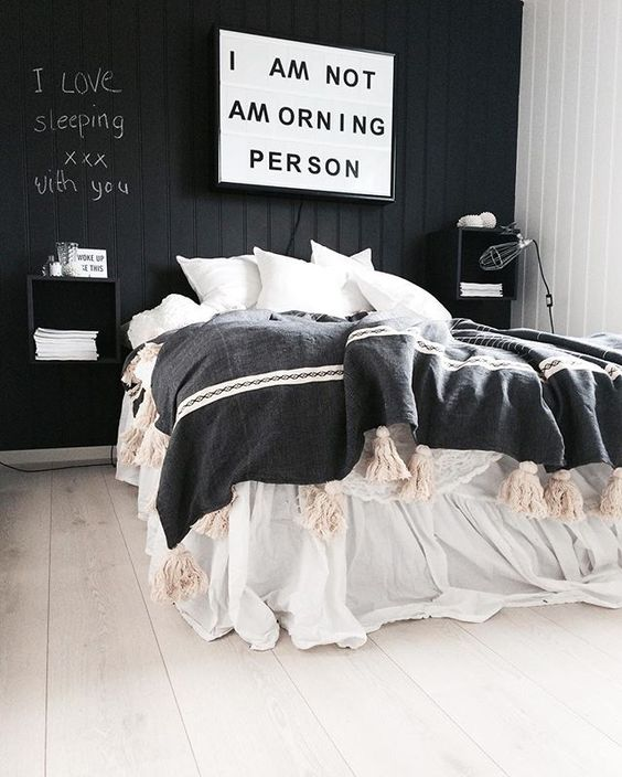 a stylish black and white bedroom with a black accent wall, black floating nightstands, chic bedding and a blanket with tassels