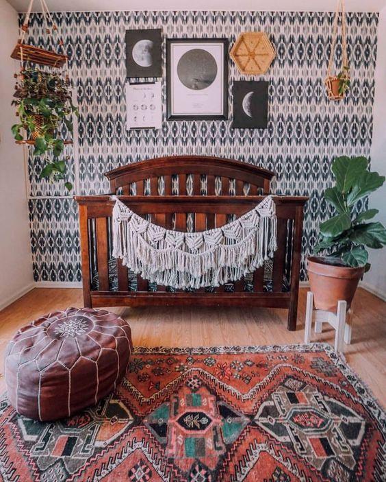 a stylish boho nursery with a monochromatic printed wall, a gallery wall, potted greenery, a boho rug and a leather ottoman