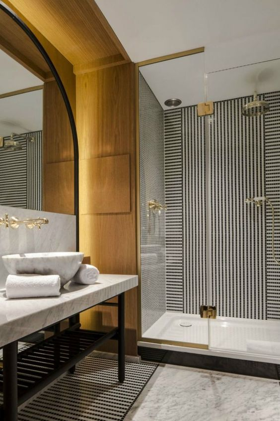 a stylish contemporary bathroom in black and white and with light colored wood, gilded touches and a statement mirror