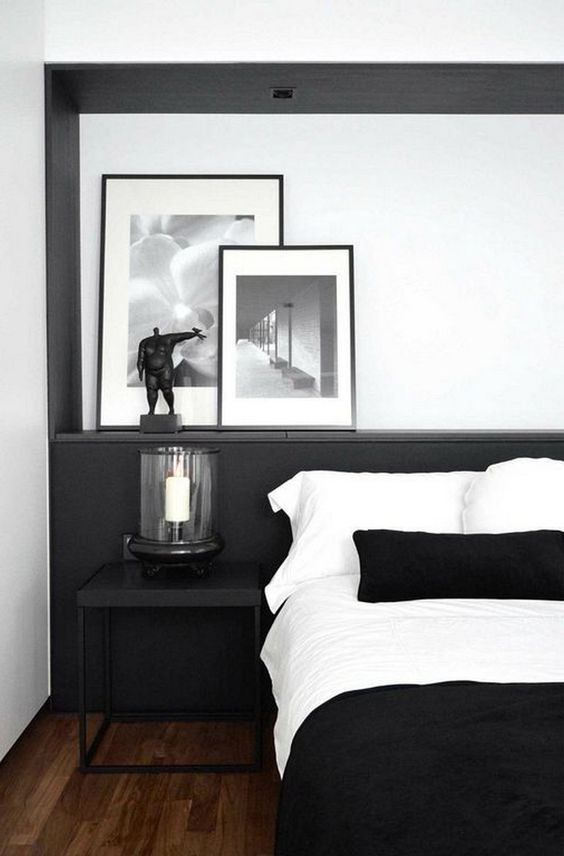a stylish contemporary black and white bedroom with a black statement wall, a candle lantern, chic artworks and monochromatic bedding