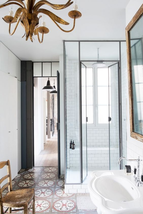 a stylish modern Parisian bathroom done in black and white, with a copper patterned floor, a gorgeous vintage chandelier and a wooden chair