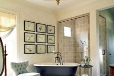 a stylish vintage bathroom with a gallery wall, a black clawfoot tub, a unique pendant lamp and some elegant furniture