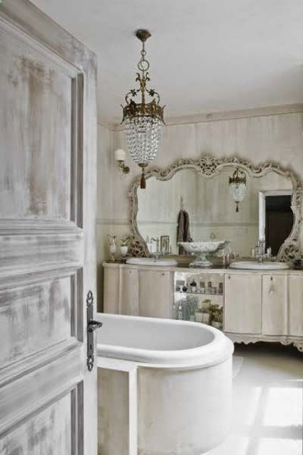 a super elegant neutral bathroom with a gorgeous crystal chandelier, a clad tub and an ornate mirror over the vanity