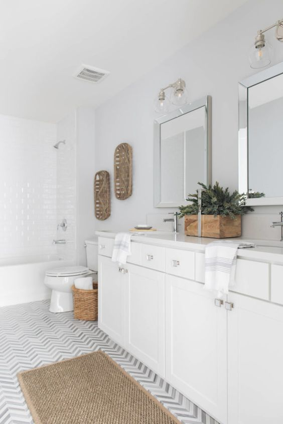 a transitional white bathroom is softened with decorative trays, a planter with greenery, a jute rug and a basket for storage