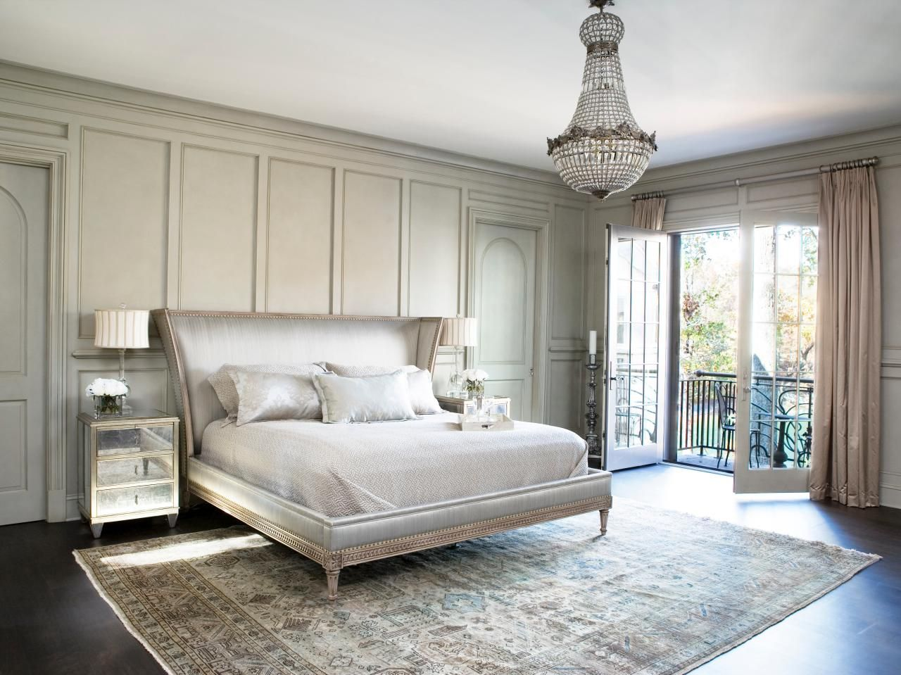 a very elegant Parisian bedroom with a printed rug, a chic upholstered bed, a crystal chandelier and mirror nightstands
