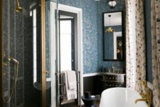 a vitnage-inspired bathroom with printed curtains, a chic black tub, gilded touches and blue printed wallpaper