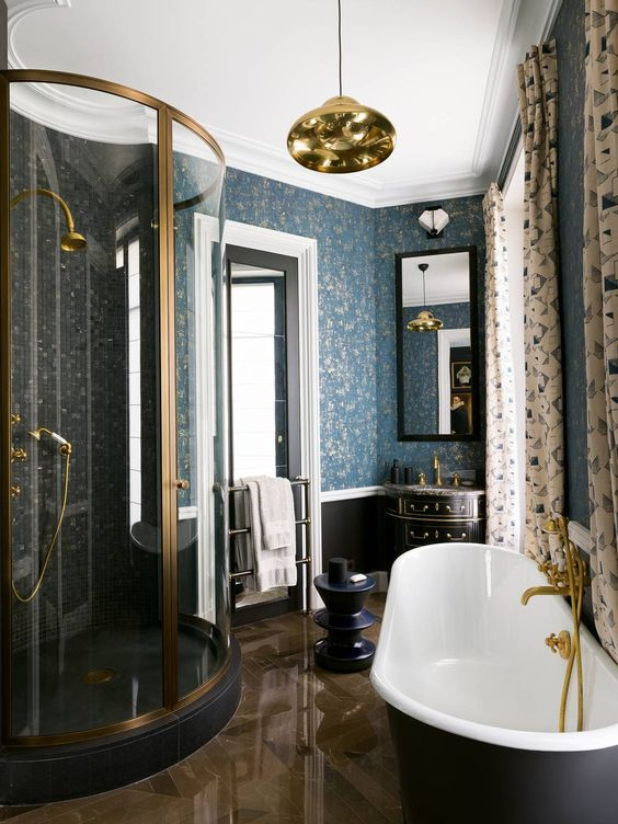 a vitnage inspired bathroom with printed curtains, a chic black tub, gilded touches and blue printed wallpaper
