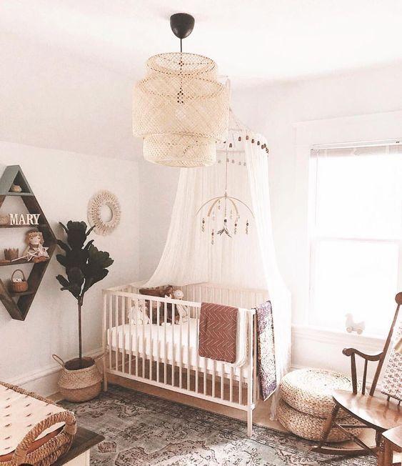 a warm-colored boho nursery with a boho rug, jute poufs, a wicker lampshade, baskets and a mobile