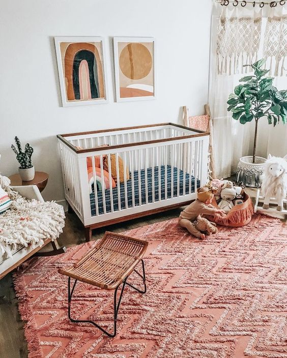 a welcoming boho nursery with artworks, macrame curtains, a reddish boho rug, a rattan stool and potted plants