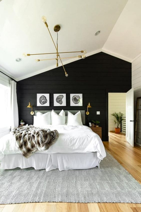 a welcoming rustic meets modern bedroom with a black shiplap wall, a neutral bed, gilded lighting fixtures and wooden nightstands
