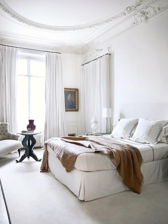a white Parisian bedroom with airy curtains, an upholstered bed, an artwork and a chic tufted chair in the corner