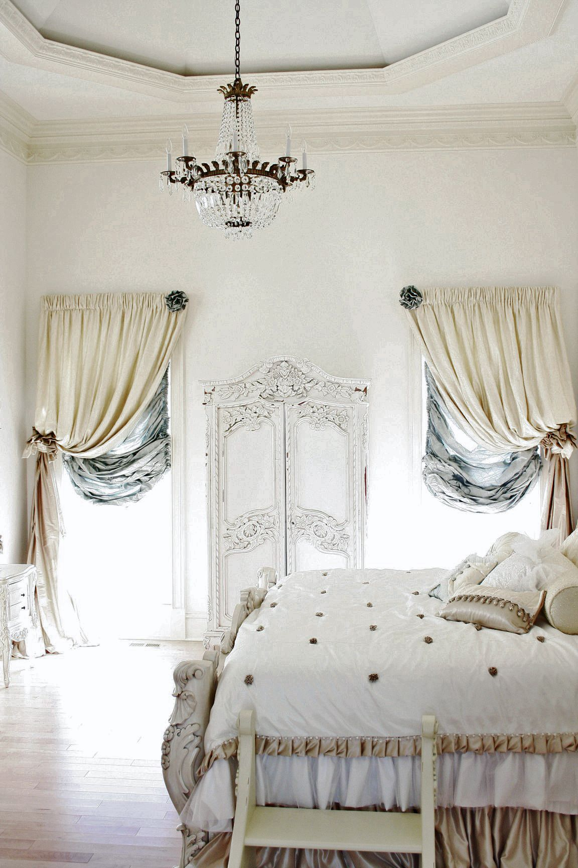 an antique inspired Parisian bedroom in neutrals and soft touches of blue, with sophisticated furniture and chic draperies