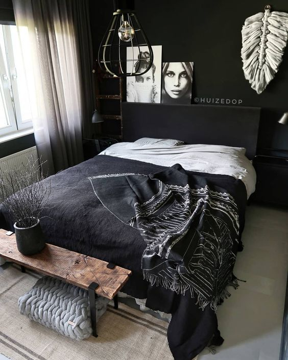 an edgy black and white bedroom with moody black walls, a black bed, a wooden bench, a unique pendant lamp and a gallery wall