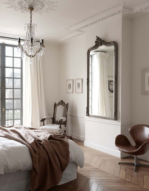 an elegant Parisian bedroom with a herringbone floor, a statement mirror, a chic crystal chandelier and a refined chair