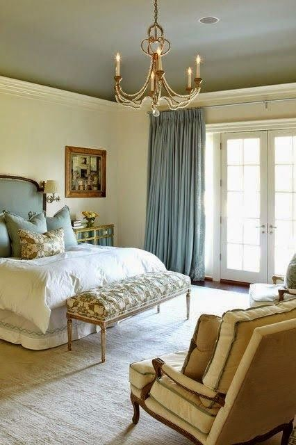 an elegant Parisian psace done with gold, beige, blues and a chic chandelier, an upholstered bench and refined furniture