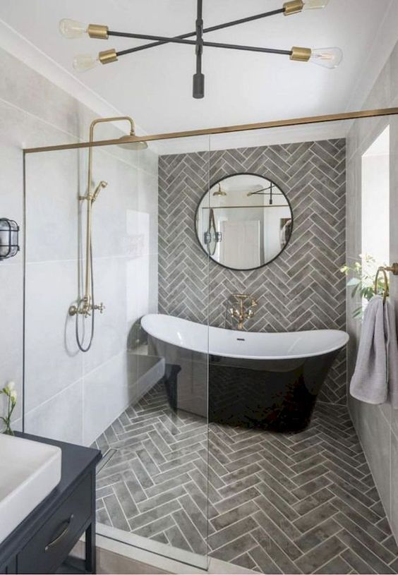 an elegant bathroom with grey tiles, a black tub, gilded touches, a black vanity and a round mirror looks super chic