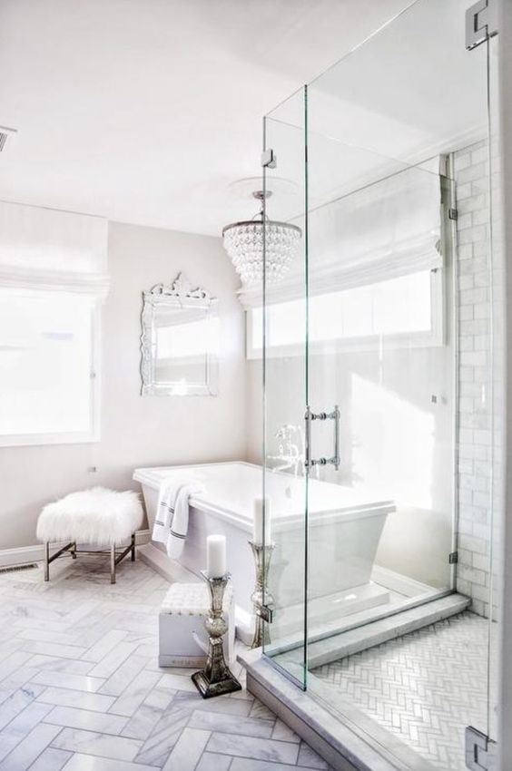 an ornate mirror, a crystal chandelier, a faux fur stool and candles plus marble tiles make the bathroom glam