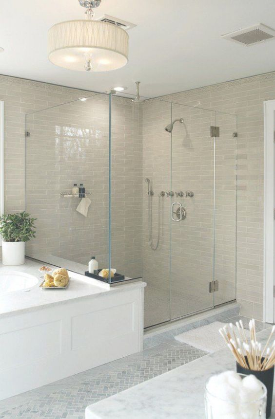 light beige tiles in the shower space and a pendant lamp add warmth and coziness to the neutral transitional bathroom