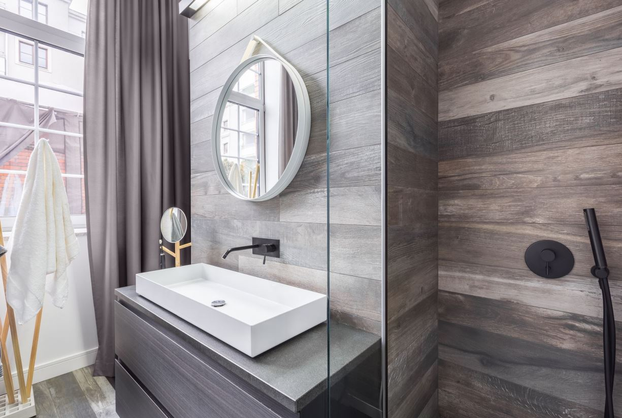 wood imitating tiles, wood grain cabinets and shelves create a very welcoming ambience making the bathroom awesome