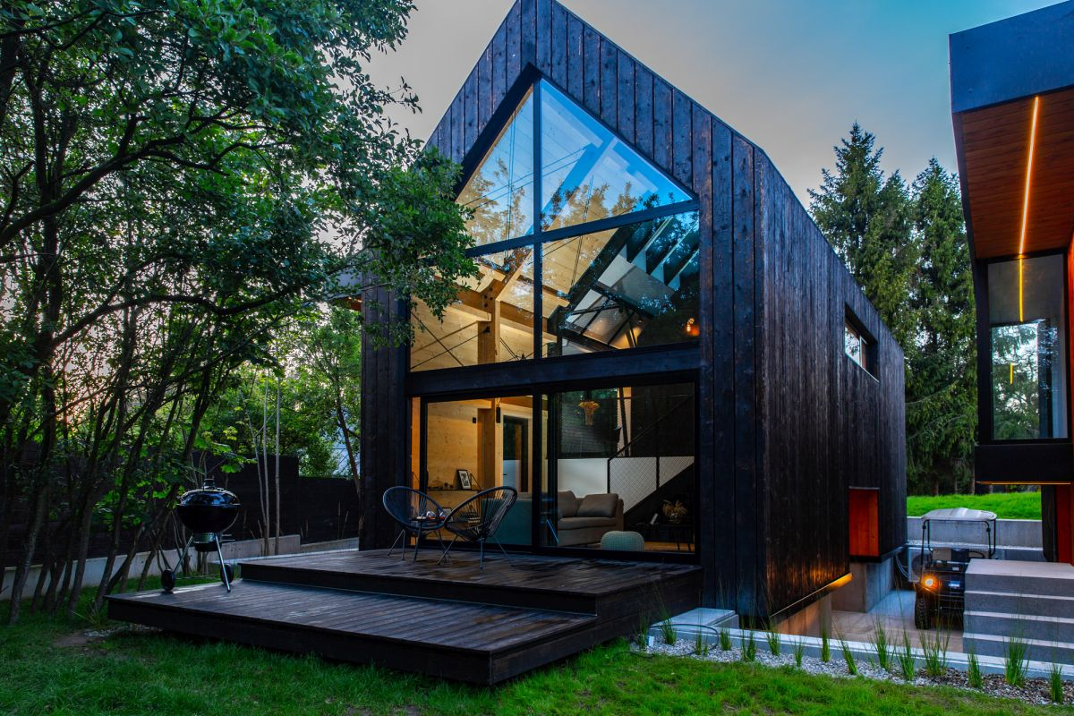 This contemporary cabin is A framed and features dark wood frames that help it better blend in with the natural surroundings