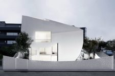 01 This unique minimalist house in white is filled with light and has a perforated facade, its interior and exterior are both unusual