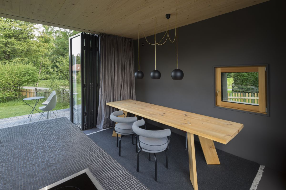 Inside the walls are also dark, the kitchen is united with the dining zone, which is highlighted with pendant lamps