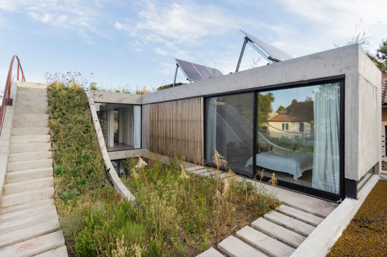 The house is built of concrete, with glazed walls and photovoltaic panels