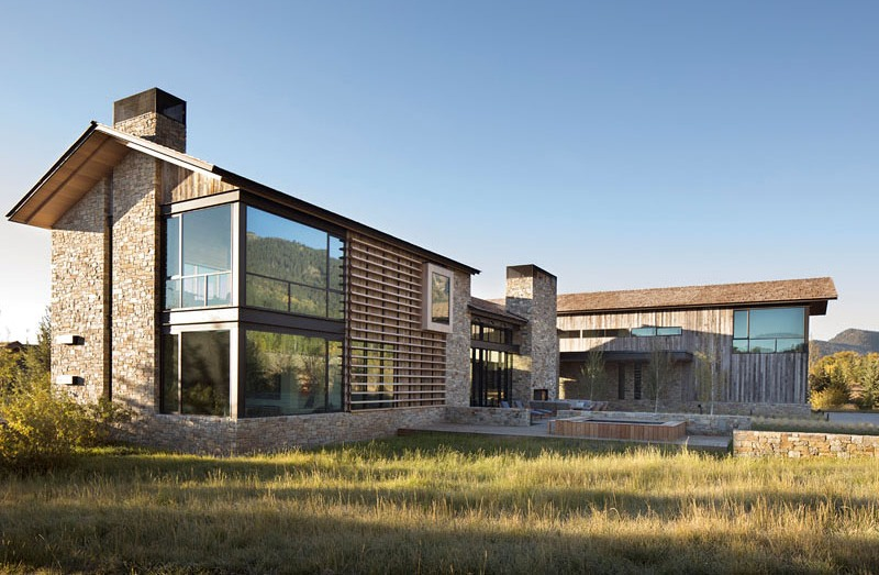 The house may resemble a modern barn of wood and stone, with glazed walls and terraces