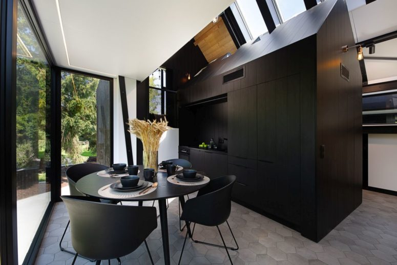 The kitchen is built as a miniature house, all black and with a roof, all the necessary things are hidden within, and the dining zone in black is here