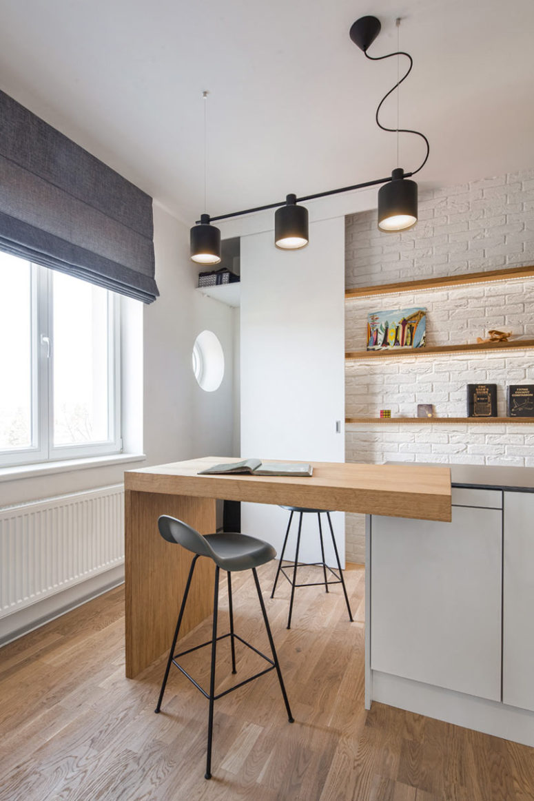 The kitchen is done with sleek minimalist cabinets, built-in shelves, a brick wall and a kitchen island that doubles as an eating space
