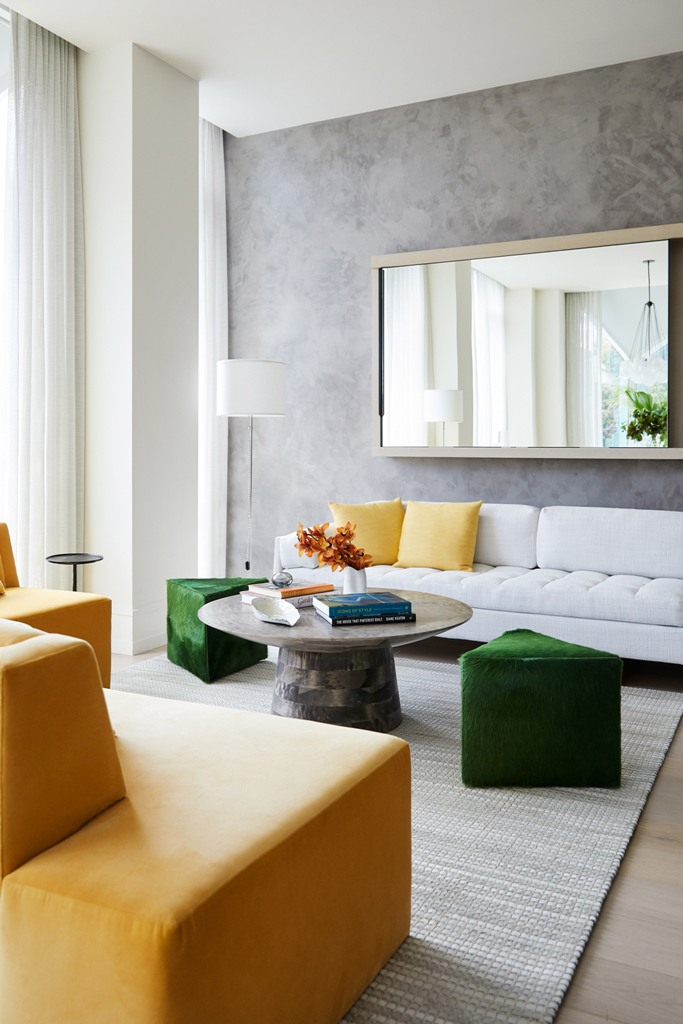 The living room is done with yellow and green touches and geometric shapes plus a statement mirror