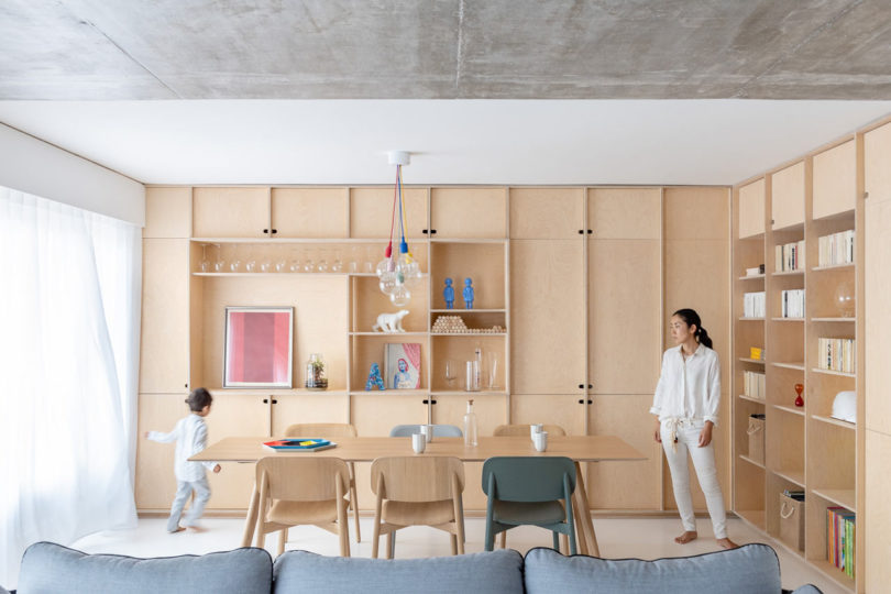 The living room is united with a dining space, there are lots of light colroed plywood cabinets for storage