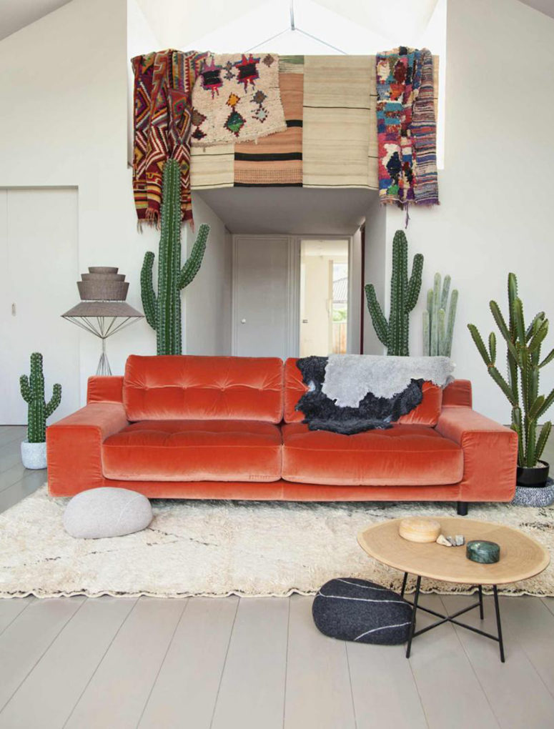 a chic orange velvet sofa makes a bold statement in the boho desert living room and becomes a centerpiece