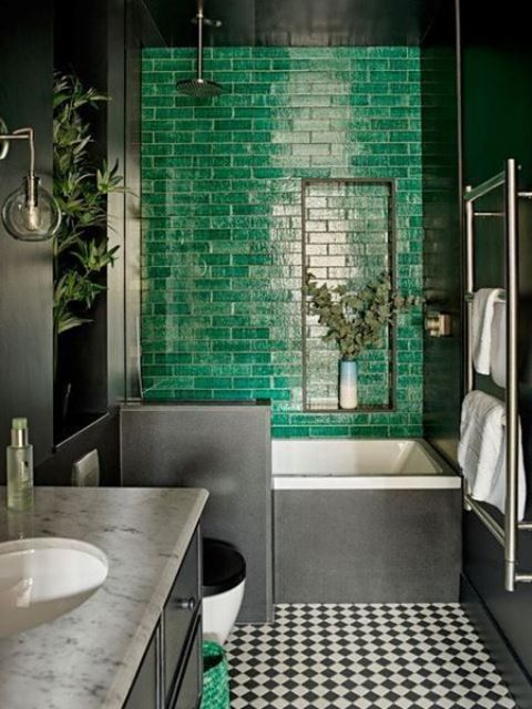 a moody bathroom with a statement emerald tile wall, a checked floor and a marble countertop looks super bold