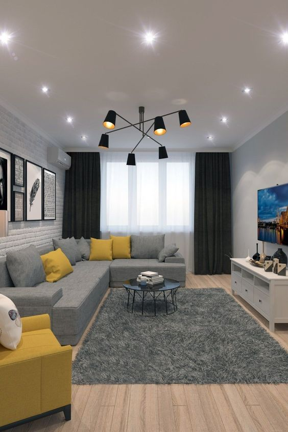 a stylish contemporary living room done with ceiling lights and a statement black chandelier wiht a mid-century modern feel