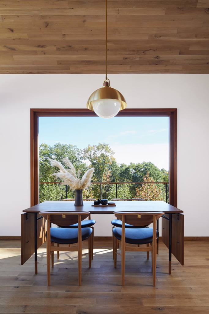 The dining space is done with a folding table and stylish leather chairs and is located next to the window to maximize the light and views
