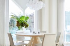 03 The dining space is done with a round table and curvy chairs plus a cluster of pendant lamps