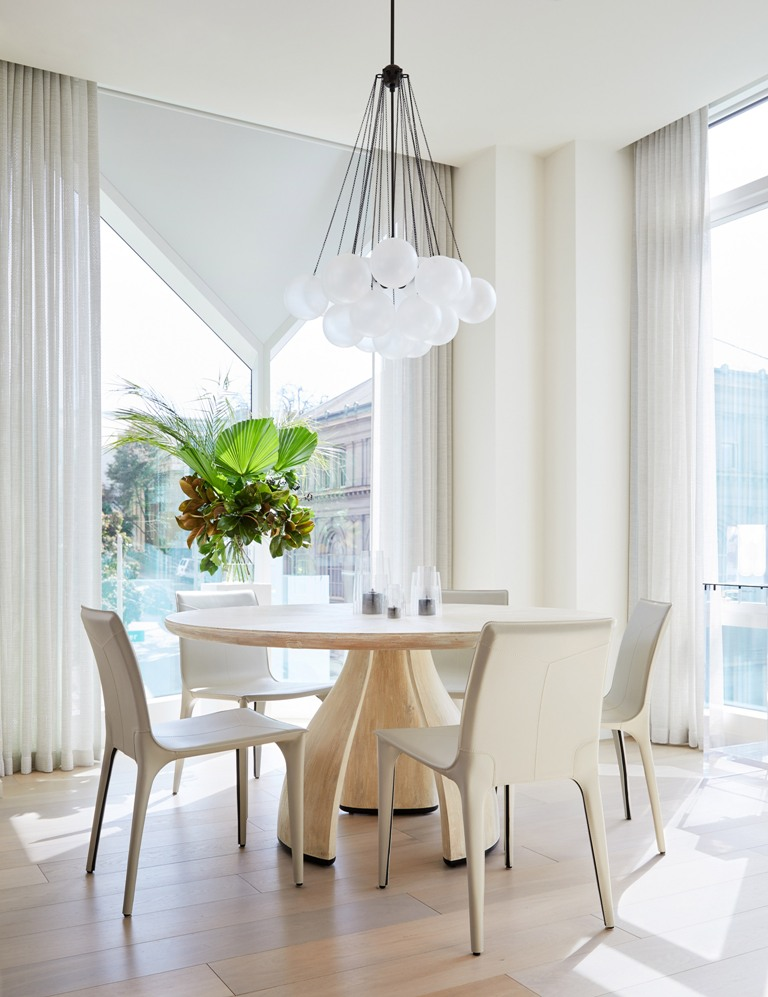 The dining space is done with a round table and curvy chairs plus a cluster of pendant lamps