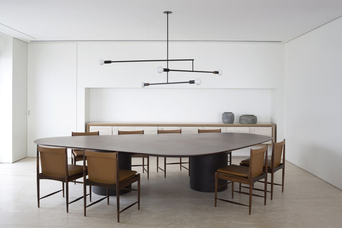 The dining table is very large and surrounded by eight elegant and comfortable chairs as the owners often have guests